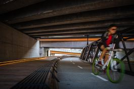 Jim Stynes Bridge - Cyclist close up under road bridge (Courtesy: Cox Architecture)