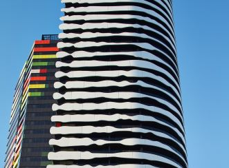 Swanston Square Apartment Tower: the facade consists of black cladding contrasted with 6-metre long white panels to make the impression of Aboriginal artist, Elder William Barak