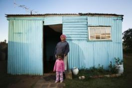 A woman and child in front of a shack in an informal settlement